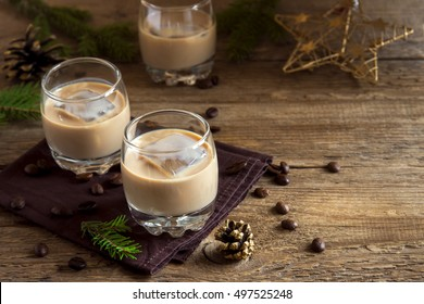 Irish cream coffee liqueur with ice, Christmas decoration and ornaments over rustic wooden background - homemade festive Christmas alcoholic drink