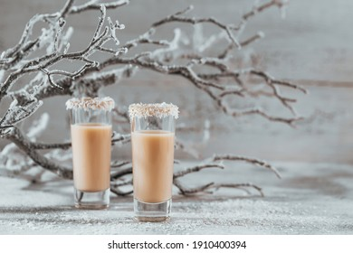 Irish cream Liquor or Coffee Liqueur with coconut flakes crown on top of short glass. Whinter holiday decorations