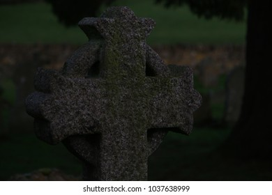 Irish Cross tombstone in an old graveyard during a brilliant sunset out in the countryside.  Brilliant golden hour sunlight streams through while the grass and plants are brilliantly green.