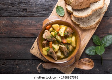 Irish dinner. Beef meat stewed with potatoes, carrots and soda bread on wooden background, top view, copy space. Homemade winter comfort food - slow cooked