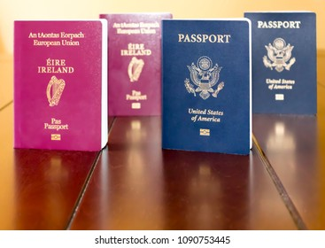 Irish (European Union) and United States of America Passports standing next to each other, and reflected on a wooden table.