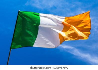 Irish flag fluttering in a brisk breeze against a bright blue sky. Europe.