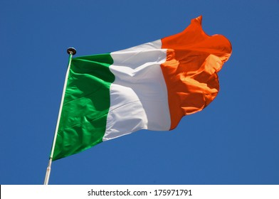 Irish flag fluttering in a brisk breeze against a bright blue sky.