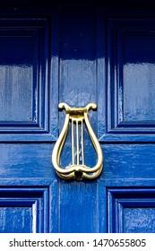 Irish harp as an ornamental door knocker on a blue wooden front door