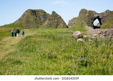 Irish landscape, green grass and cave-like rock formations, hiking family