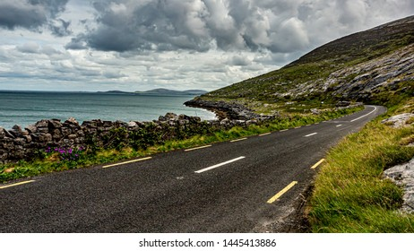 Irish landscape with the sea and the rural coastal R477 road along the Burren, geosite and geopark, Wild Atlantic Way, cloudy spring day in county Clare, west coastal of Ireland