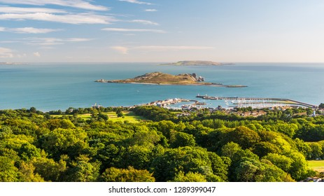 Irish landscape as seen from the Ben of Howth with green trees, turquoise sea waters and Ireland's Eye Island in the distance on a beautiful summer day.