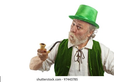 Irish leprechaun with white beard, top hat, and green velvet vest. He holds up curved pipe, raises eyebrows, purses lips and tilts head. Isolated on white, horizontal layout with copy space.