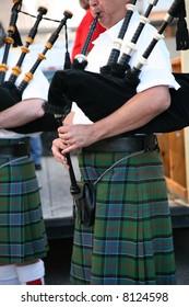 Irish man in his kilt playing his bagpipe