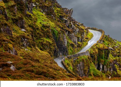 Irish road with mountain view, Countryside Country Road Or Lane And Dry Stone Wall Through Scottish Rural Lanscape At Dusk Panoramic coastal road in Dingle Peninsula .Ireland