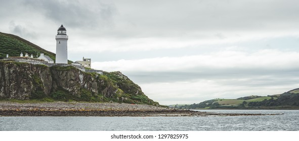 Irish shoreline panorama with Campbeltown lighthouse. Northern Ireland. Stunning English landscape. White lighthouse on the steep cliff. The shore panoramic view under the rainy cloudy sky.