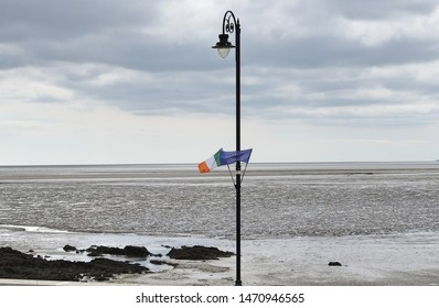 The Irish tricolour flag and European Union EU flag on a lamp post along the promenade  overlooking the beach in Blackrock, Dundalk, County Louth, Ireland.