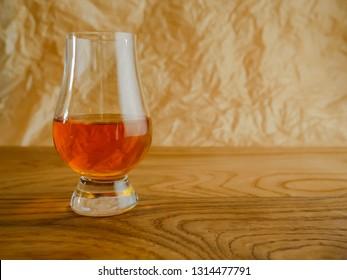 Irish Whiskey Glass on Wood and Paper Background Medium Shot