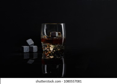 Irish whiskey. Glass of whisky with wiskey stones. Wiskey stones on black background. Elegant glass of whiskey .
