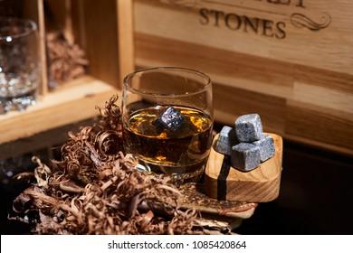 Irish whiskey. Glass of whisky with wiskey stones. Elegant glass of whiskey with Whiskey stones. Scotch Whisky in the glass. Irish Whiskey with oak box.