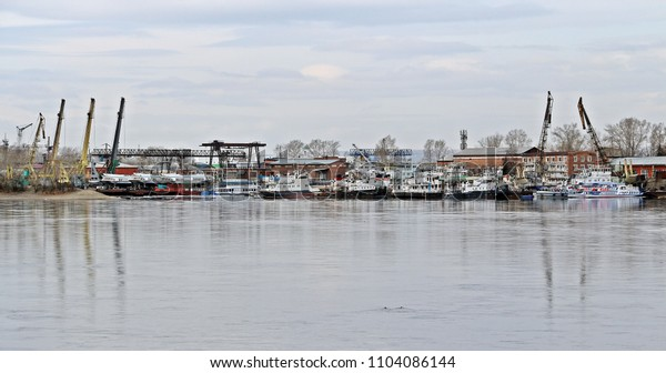 IRKUTSK, RUSSIA - April 11, 2018: Viewed to cargo shipyard of Irkutsk city along Angara river, Siberian area. Lots of ships park for maintenance and transfering