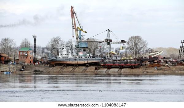 IRKUTSK, RUSSIA - April 11, 2018: Viewed to cargo shipyard of Irkutsk city along Angara river, Siberian area. Lots of ships park for maintenance and transfering