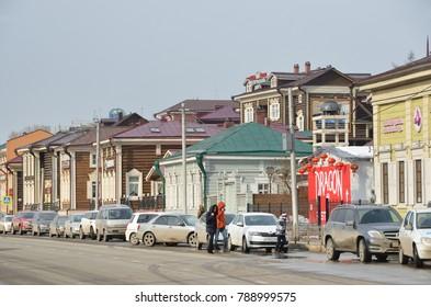 Irkutsk, Russia, March, 17, 2017.Irkutsk, cars near old styled wooden houses on street of 3-th July in the 130-th quarter
