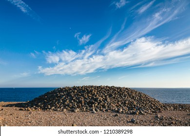 Iron Age cairn made of cobble deposits from the recent ice age on Molen beach of rolling stones at UNESCO Global Geopark near Larvik, Vestfold County, Norway