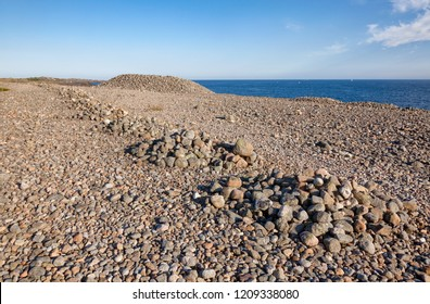 Iron Age cairns made of cobble deposits from the recent ice age on Molen beach of rolling stones at UNESCO Global Geopark near Larvik, Vestfold County, Norway