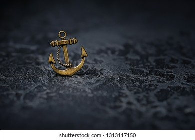iron anchor on black background. Metallic small anchor necklace on black. symbol of sailors, reliability and confidence, naval theme. concept of travel. copy space