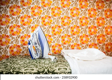 an iron appliance over a wall covered with retro styled floral wallpaper