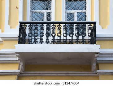 Iron balcony on the yellow plastering wall.