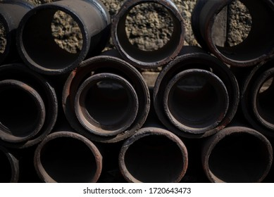 Iron barrels are arranged in a regular pattern in the street. Textured background.
