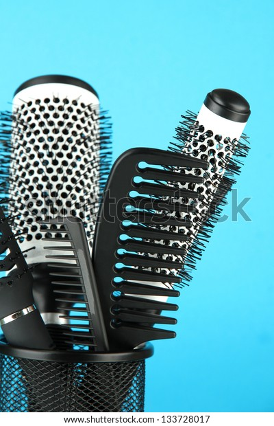 Iron basket with combs and round hair brushes, on color background