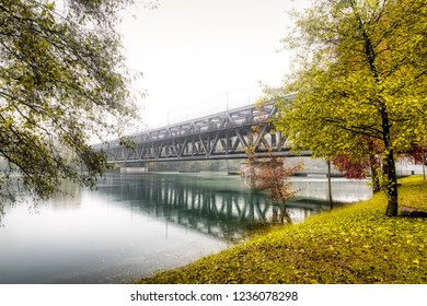 iron bridge on Ticino river in flood during the rainy season with milky sky in background