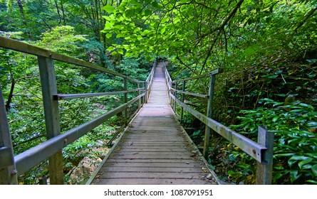 Iron bridge over dry stone riverbed in sunny summer Abkhazia