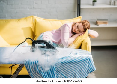 iron burning on shirt while woman sleeping on sofa at home