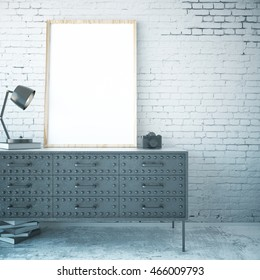 Iron cabinet with blank picture frame, lamp, books and camera in room with concrete floor and white brick wall. Mock up, 3D Rendering