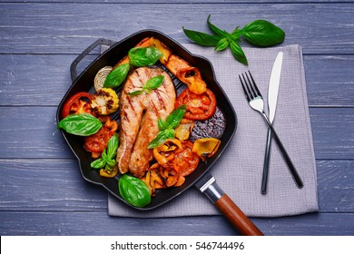 Iron cast pan with slice of red fish and vegetables on napkin