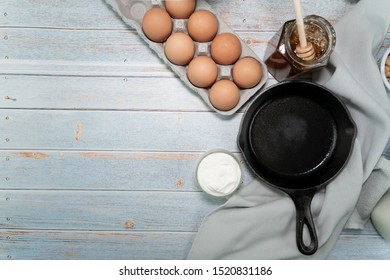 an iron cast skillet on rustic wood table with organic eggs, sour cream, honey, milk
