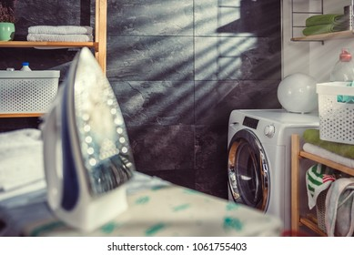 Iron and cloth on ironing board at laundry room with washing machine by the window visible in the background