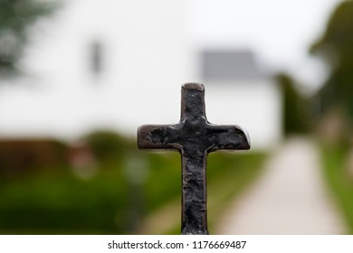 Iron cross in front of blurred church building.