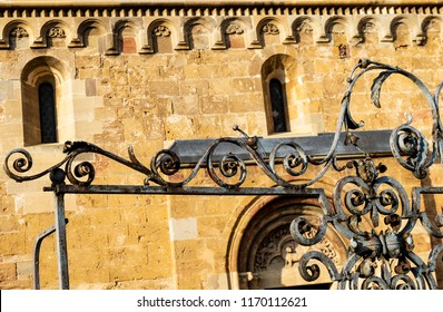 iron decoration and an old romanesque church in the background