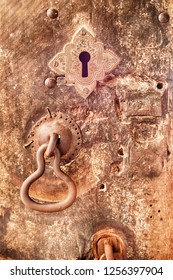 An iron door knocker and a keyhole adorn a battered wooden door at the Dambulla cave temple in Sri Lanka