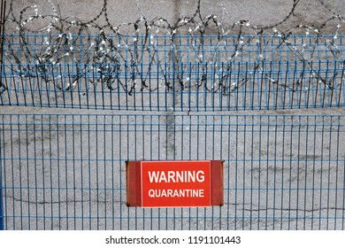 Iron fence with barbed wire. Metallic fence with red warning sign Quarantine.
