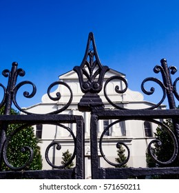Iron fence behind St. Louis Catedral that surrounds a gardens of the church  located in the French Quarter in New Orleans.  St. Louis Cathedral is the oldest Cathedral in the United States.