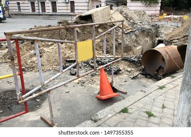 iron fence near the place of replacement of water pipes. sewage pipe in the hole on the construction side