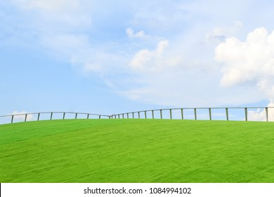 Iron fence on green grass and blue sky wallpaper