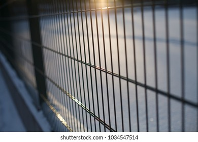 Iron fence of thin rods with a glare of the sun and blurred snow phonemes behind