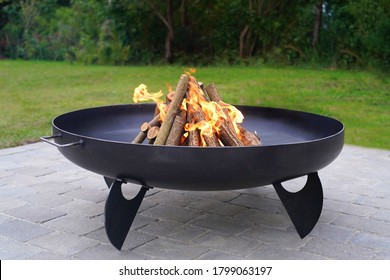 Iron fire pit and burning fire in  a garden .