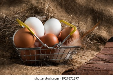 iron food basket with brown and white eggs on a brown wooden background with burlap.