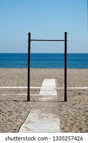 Iron frame surrounding a wooden way on the beach. It is looking like a portal leading to the sea.