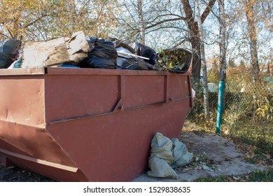 An iron garbage can of red color is overflowing with bags of tree branches and leaves. Overflowing with garbage.