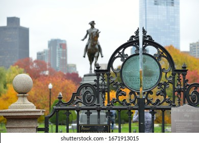 Iron gate and fall colors in Boston Public Garden. George Washington statue and city skyline in background.