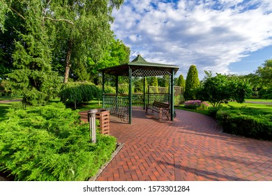 an iron gazebo with a bench and paving stone tiles in the garden with a lawn and evergreen thuja on a sunny day with a cloudy sky, nobody.